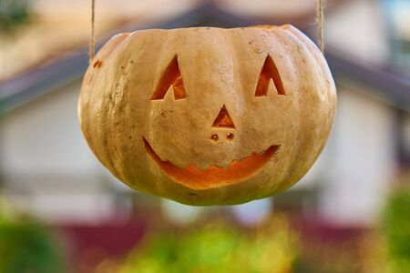 Halloween pumpkin is suspended on ropes on the background of the house.