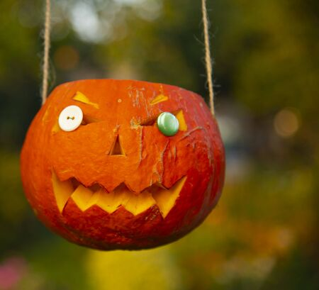 Bright orange Halloween pumpkin, carved with his own hands, suspended on ropes, on a blurred background Stock fotó
