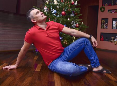 A smiling man in a red t-shirt sits under a decorated Christmas tree. New year holiday.