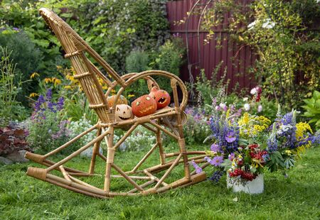 Halloween pumpkins lie in a wicker rocking chair that stands on the lawn.Next to it is an enamel pot with a bright autumn bouquet