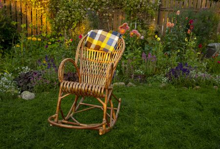 A wicker rocking chair sits on a lawn in a blossoming garden.A plaid wool blanket is draped over the back of the chair.
