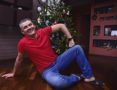 A man sits under a decorated Christmas tree