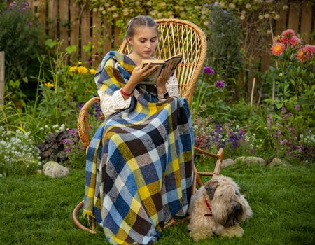 Beautiful girl sitting in a wicker rocking chair with a book.Next to the dog.