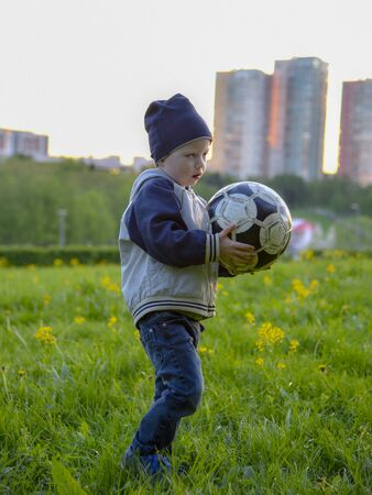 A small child in a cap playing on the grass with a ball. On a blurred background of city houses and people Stockfoto