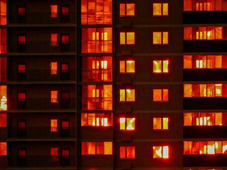 Istantanea notturna. Scuri grattacieli residenziali, in cui la luce rossa Finestre e balconi. Fotografia a contrasto.