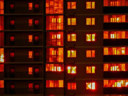 Night snapshot. Dark residential high-rise buildings, in which red light Windows and balconies. Contrast photography.