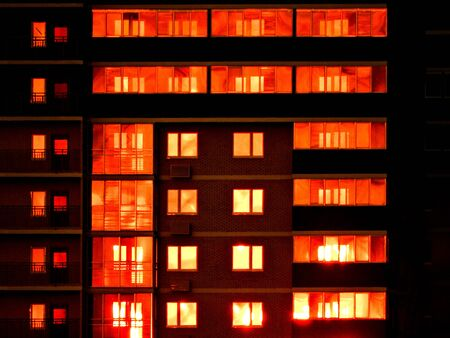 Night snapshot. Dark residential high-rise buildings, in which red light Windows and balconies. Contrast photography. Banque d'images - 130104650