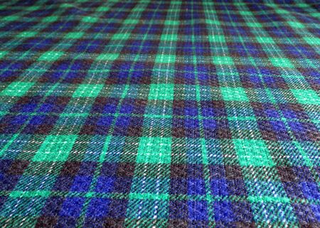 A fragment of a woolen blanket.Checkered blue-green background. textured material