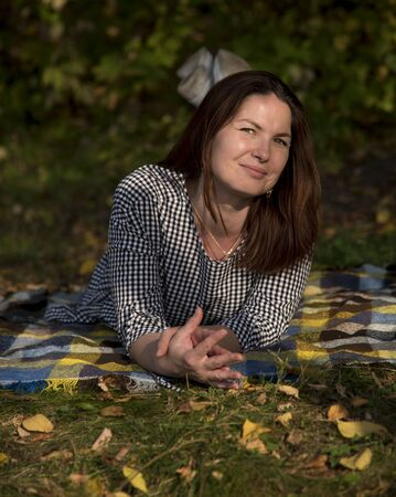A smiling forty-year-old beautiful woman with her hair down and a plaid tunic lies on a wool blanket in the Park. It's surrounded by yellow autumn leaves.