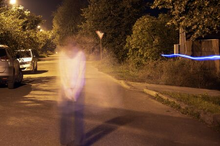 Photo taken at night at long exposure.A country road on which stands a man who looks like a phantom. Item freezelight.