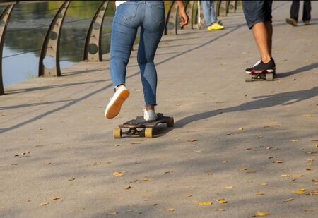 fragment of the embankment strewn with yellow leaves.People go along the waterfront on a skateboard, photographed from the waist down. Foto de archivo