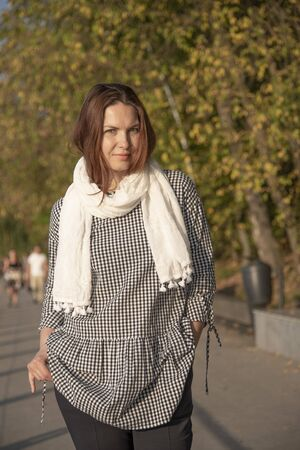 A middle-aged woman in a plaid tunic and white neckcloth stands on the waterfront with her hands in her pockets.She has a bully look on her face.