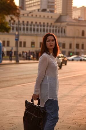 A single woman 40 years old in a white blouse posing in the city streets and looks at the camera, the city is illuminated by the sunset rays. 版權商用圖片