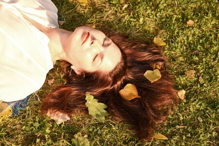 A woman lies on the ground with her eyes closed and enjoys the sun's rays. Her red hair are the leaves of the trees.