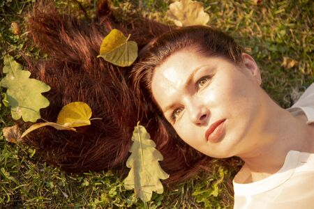 A Portrait of a woman lying on the ground, autumn leaves scattered in her hair. 写真素材
