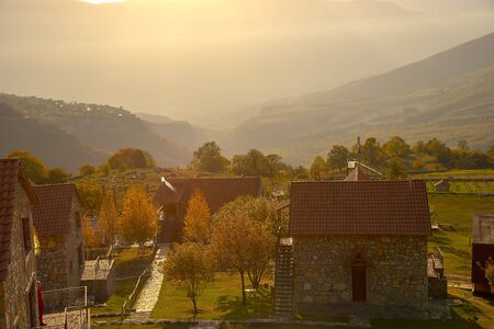 Sunrise over the mountains and the village.Autumn landscape.In a light misty haze. Stock Photo