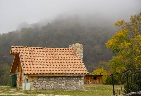 Autumn landscape.Stone house with a tiled roof on the background of wooded mountains.A thick fog descends on the mountains.