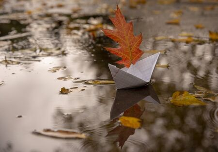 A paper boat made from a notebook sheet floats in a puddle, instead of a sail it has a red oak autumn leaf. Stock fotó
