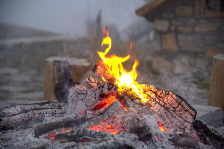 The dying fire, wood, coals and ashes.Thick smoke over the fire, in the background the stone wall of the house and the fog.