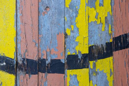 Multicolored wooden background of old boards with peeling paint.