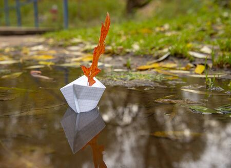 The paper boat from a notebook sheet floats on an autumn puddle, being reflected in water. Instead of a sail, a red oak leaf. Stok Fotoğraf