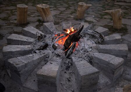 Bonfire, burning woodpile and round of stones, campfire or fireplace. On firewood