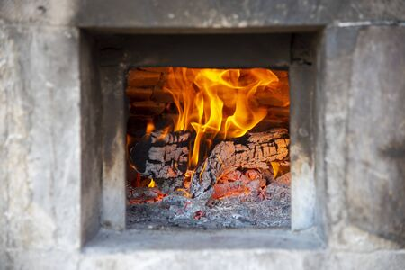 The firebox of the stove in which burns a bright fire.  Reklamní fotografie