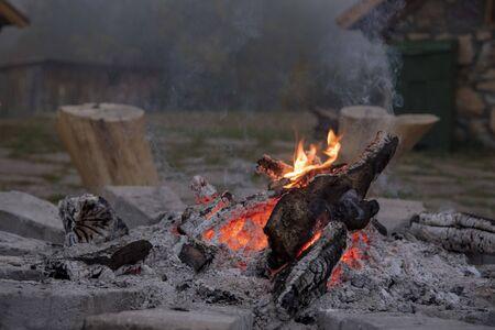 Un feu mourant dans les rochers.Bois brûlant, charbons et cendres au centre. La fumée vient du feu. Brouillard en arrière-plan. Banque d'images