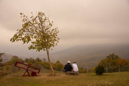 Autumn landscape. Two sit on a bench on the hillside, near a tree and a swing.Fields and mountains stretched before them. A thick fog descends. 写真素材
