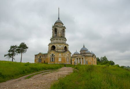 The Church stands on a hill, and is accessed by dirt road, around the green grass.