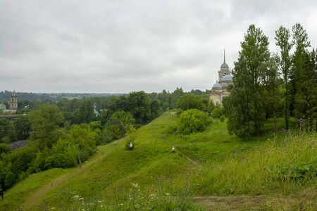 Summer landscape.A hill covered with green grass, a path and a Church at the top, hidden behind trees. 写真素材