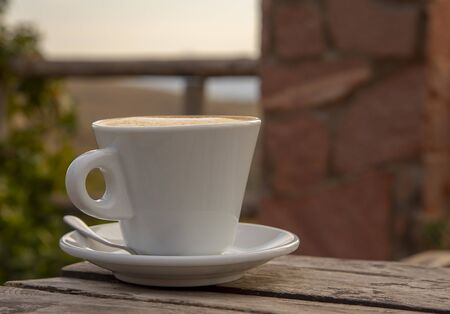 A cappuccino Cup with saucer and spoon sits on an old wooden table outside on a Sunny day.