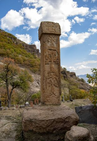 Khachkar is a type of Armenian architectural monuments made of stone, against a mountain landscape.