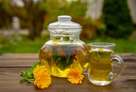 Transparent teapot and a Cup of herbal tea on a wooden table on a blurred background.Lay next to the calendula flowers. Banco de Imagens - 133303664