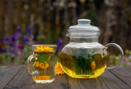 Transparent teapot and a Cup of herbal tea on a wooden table on a blurred background.Lay next to the calendula flowers. Banco de Imagens - 133303671
