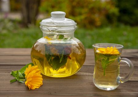 Transparent teapot and a Cup of herbal tea on a wooden table on a blurred background.Lay next to the calendula flowers.