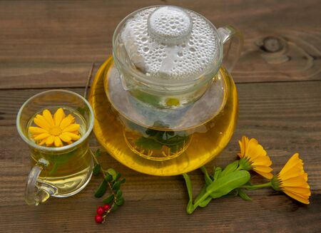 Transparent teapot and Cup of herbal tea on wooden background. Near the flowers of calendula and cranberries. The view from the top. Banco de Imagens - 133303794