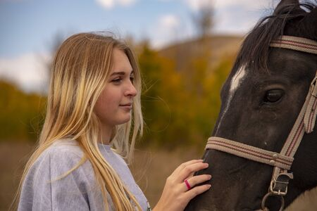 A young girl with long blond hair gently strokes the brown horses muzzle.