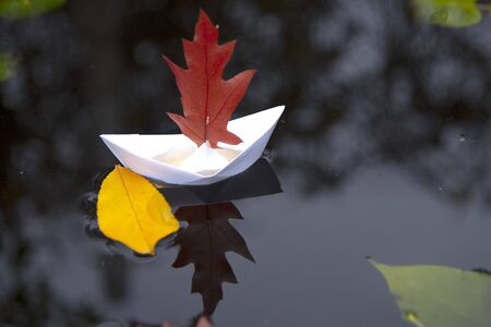 A white paper boat with an oak leaf instead of a sail on black water, a yellow autumn leaf floats nearby. Banque d'images - 132917456
