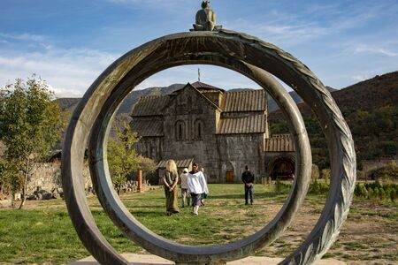 Armenia, Akhtala, October 2019. a stone sculpture symbolizing the engagement rings, one can see people walking towards the temple, standing against the backdrop of autumn mountains. Stockfoto