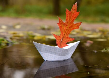 The paper boat from a notebook sheet floats on an autumn puddle, being reflected in water. Instead of a sail, a red oak leaf. Banque d'images - 133033538