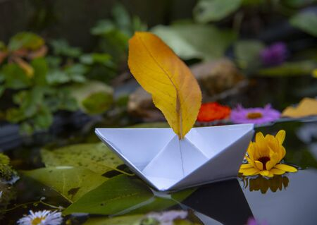 A white paper boat with a yellow sail made of autumn leaves lurched in the water. fallen leaves and bright flowers float around. Banque d'images - 133077395