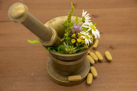 In a metal mortar lie medicinal herbs, and next to the wooden background pills. Reklamní fotografie