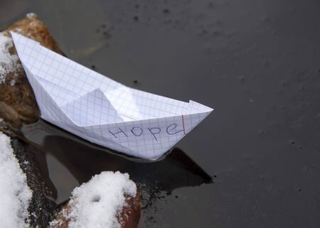 A paper boat made of a checkered notebook with the inscription HOPE stuck in the ice.