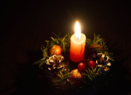 One burning candle in a Christmas wreath on a dark background.