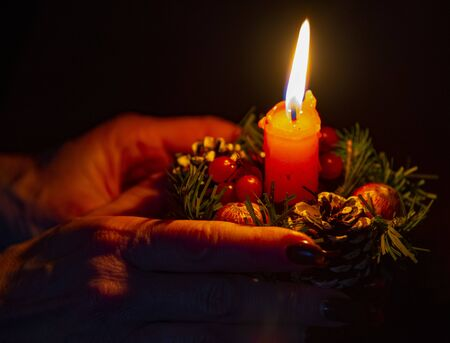Hands of an elderly woman holding a Christmas candle. on dark background.