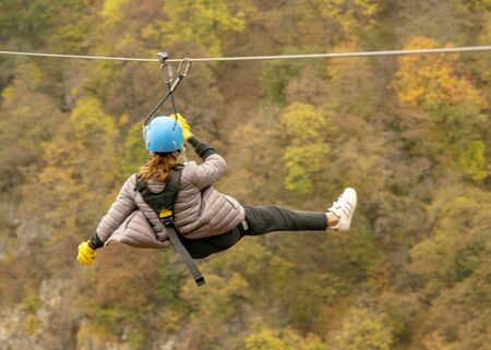 A teenage girl flies on a zipline against the background of mountains covered with autumn forest.