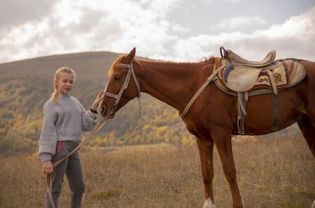 A teenage girl stands in a field with a horse and holds it with one hand under the bridle, and the second strokes the muzzle. On the background of autumn landscape.