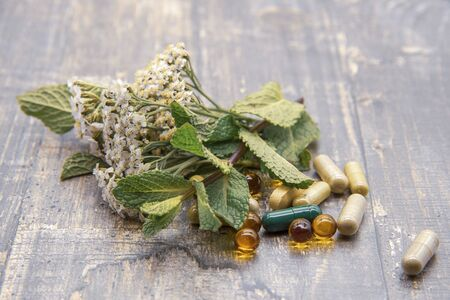 On the wooden surface are various tablets and capsules and fresh herbs and flowers. Background health. Stock fotó