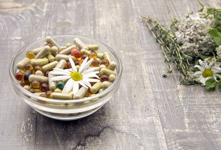 A bowl with various capsules and tablets, medicinal and aromatic herbs. on wooden background